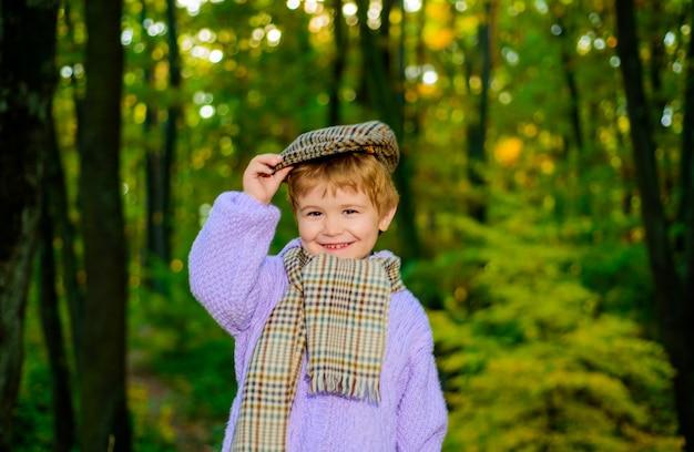 Śliczny chłopiec na jesiennym tle mały chłopiec w parku śliczny chłopiec w jesiennym parku jesienny chłopiec piękny