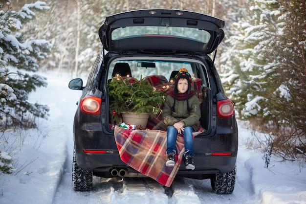Śliczny chłopiec obsiadanie w czarnym samochodzie przy śnieżnym zima lasem. koncepcja bożego narodzenia.