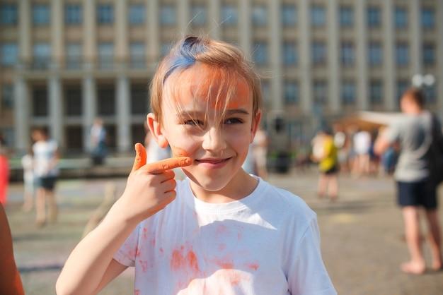 Śliczny chłopiec pomalowany w barwach festiwalu holi. szczęśliwe dzieciństwo. pre teen chłopiec bawi się kolorowym proszkiem. koncepcja indyjskiego festiwalu holi. święto holi.