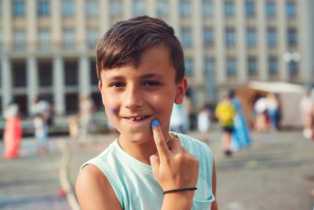Śliczny chłopiec pomalowany w barwach festiwalu holi. szczęśliwe dzieciństwo. pre teen chłopiec bawi się kolorowym proszkiem.
