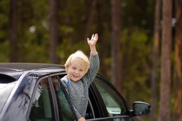 Śliczny chłopiec przygotowywający dla wycieczki samochodowej lub podróży