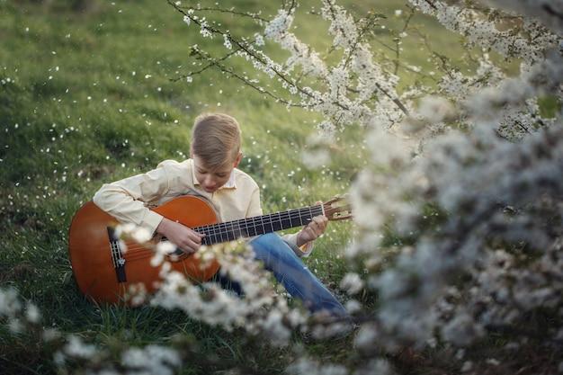 Śliczny chłopiec robi muzyce bawić się gitarę na naturze.