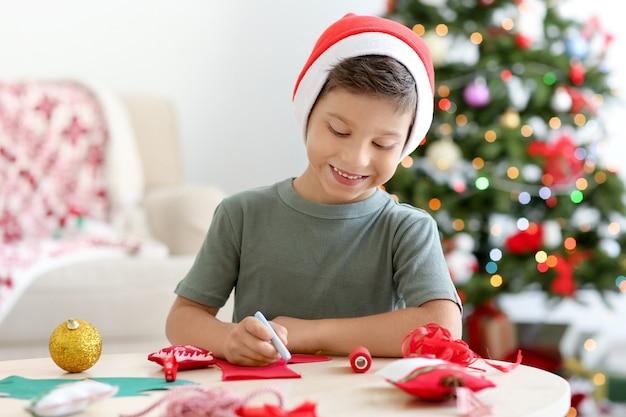 Śliczny chłopiec robi świąteczną skarpetę z filcu na stole