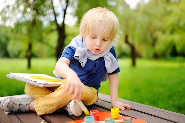 Śliczny chłopiec rysunek z kolorowymi farbami w lato parku