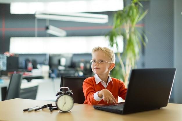 Śliczny chłopiec siedzi przy biurkiem w biurze i używa komputer