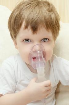 Śliczny chłopiec siedzi w domu na kanapie i oddycha przez inhalator nebulizatora. chłopiec leczy inhalator na kaszel.