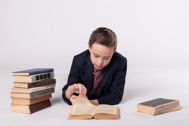 Śliczny chłopiec w garniturze leży i czyta książkę na białym tle