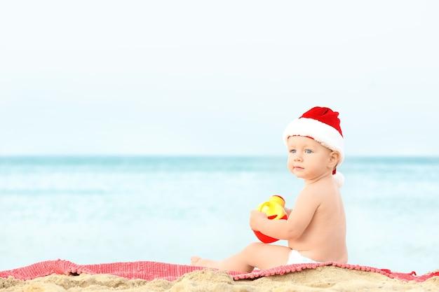 Śliczny chłopiec w santa hat na plaży