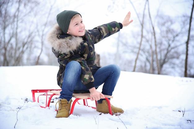 Śliczny chłopiec z saniami w snowy parku na ferie zimowe