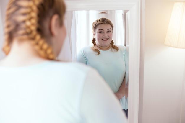 Śliczny dołek. pulchna uśmiechnięta kobieta odwracająca się w lewo do lustra ukazującego jej dołeczek