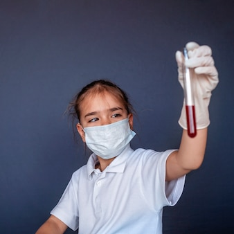 Śliczny dzieciak jest ubranym maskę respiratora i medycyn rękawiczki trzyma wynik badania krwi