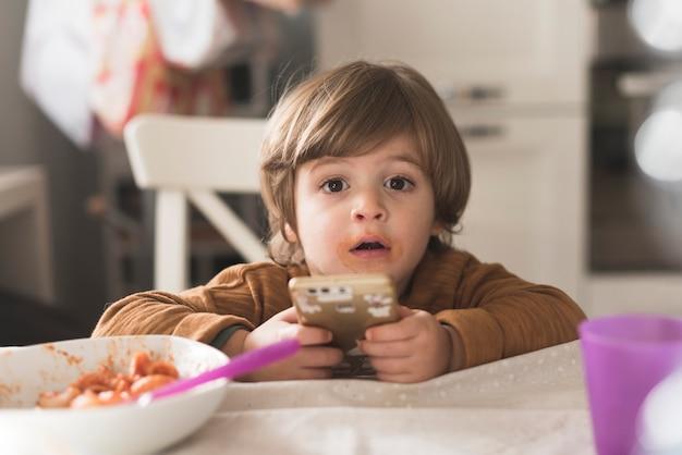 Śliczny dzieciaka mienia telefon przy stołem