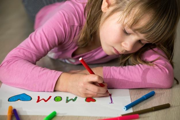 Śliczny dziecko dziewczyny rysunek z kolorowymi kredkami kocham mamy na białym papierze