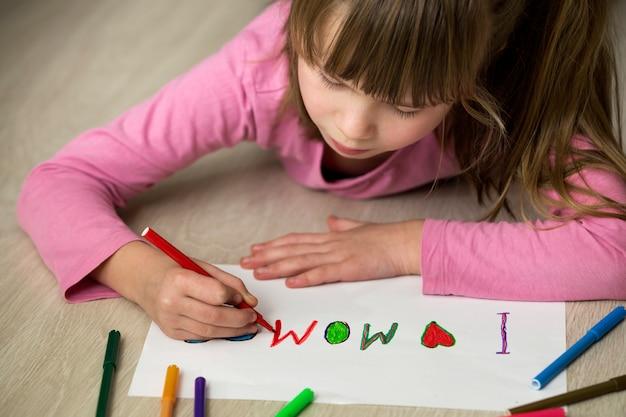 Śliczny dziecko dziewczyny rysunek z kolorowymi kredkami