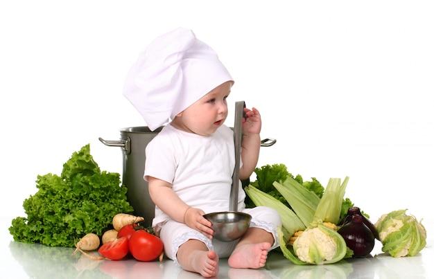 Śliczny dziecko szef kuchni z dużym garnkiem i warzywami