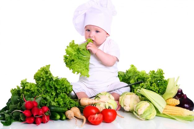 Śliczny dziecko szef kuchni z różnymi warzywami