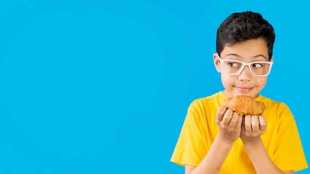 Śliczny dziecko trzyma croissant kopii przestrzeń