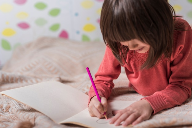 Śliczny dziewczyna rysunek na papierze na łóżku