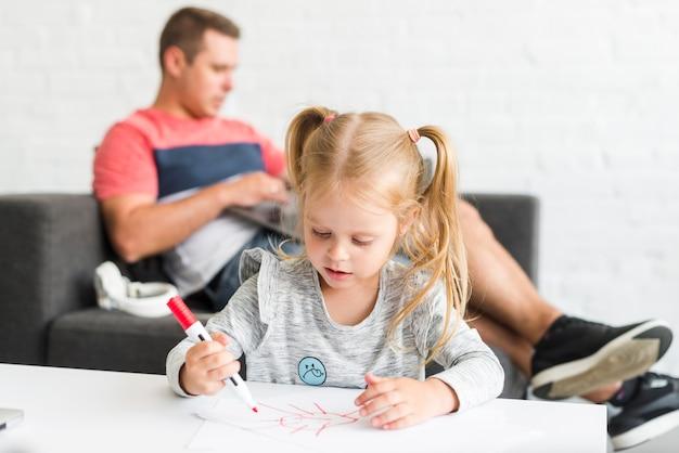 Śliczny dziewczyna rysunku nakreślenie z markierem w domu