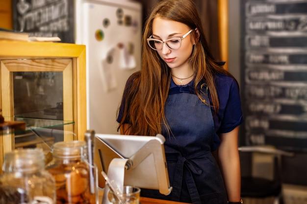 Śliczny dziewczyny barista liczy rachunek w kawiarnia na pastylce