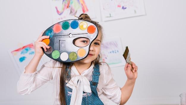 Śliczny dziewczyny obsiadanie z paletą i farby muśnięciem