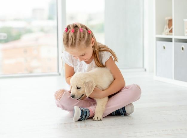 Śliczny dziewczyny obsiadanie z uroczym szczeniakiem