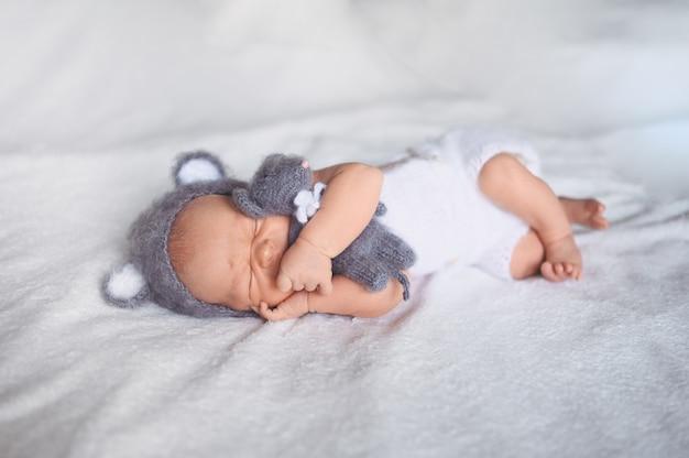Śliczny emocjonalny noworodek chłopczyk śpi w łóżeczku w garniturze z dzianiny z zabawkami.
