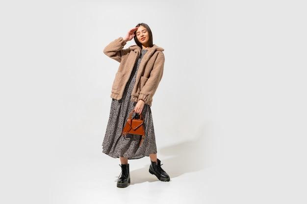 Śliczny europejski model w stylowym futrze i sukience. nosi botki z czarnej skóry. trzyma brązową torebkę.