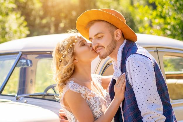 Śliczny facet i dziewczyna blisko samochodu na słonecznym dniu