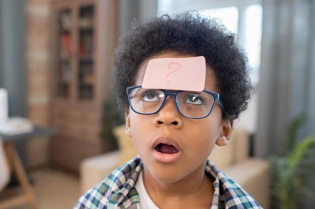 Śliczny i zabawny chłopiec rasy mieszanej w casualwear i okularach, patrzący na papier listowy ze znakiem zapytania na czole w środowisku domowym