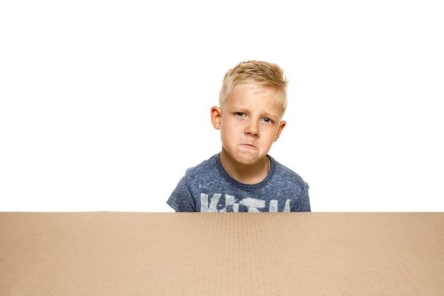 Śliczny i zdenerwowany chłopiec otwierający największą paczkę pocztową.