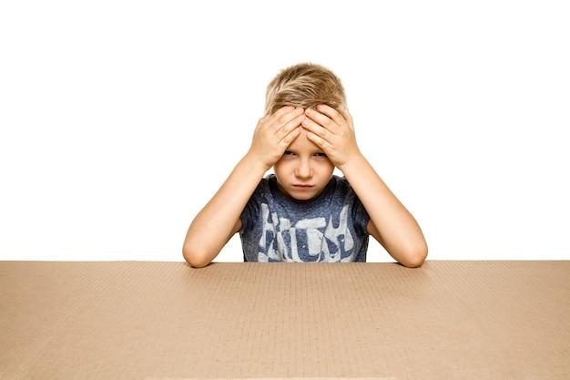 Śliczny i zdenerwowany mały chłopiec na największej paczce pocztowej. rozczarowany młody męski model na górze kartonu patrząc do środka.