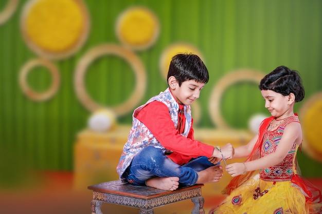 Śliczny indyjski brat i siostra świętują festiwal raksha bandhan,