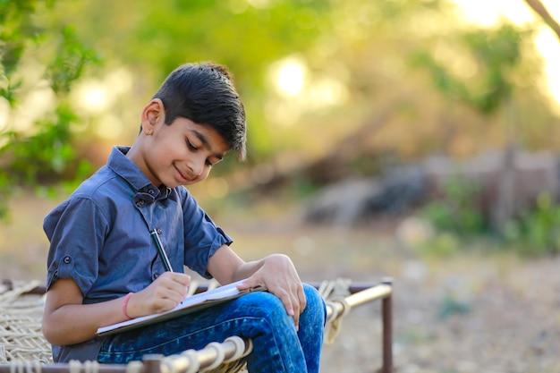 Śliczny indyjski dziecko robi jego pracie domowej w domu