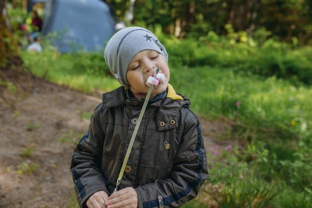 Śliczny kaukaski chłopiec je pieczone prawoślazu nawleczone na szpikulec