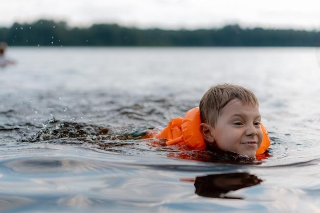 Śliczny kaukaski chłopiec pływa w kae w żywej kamizelce