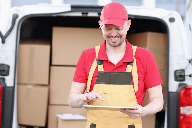 Śliczny kaukaski listonosz w garniturze i czapce sprawdza skrzynki pocztowe z tabletem w rękach
