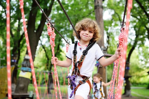 Śliczny kędzierzawy dziecko w linowym parku