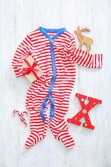 Śliczny kombinezon dla niemowląt na drewnianym tle