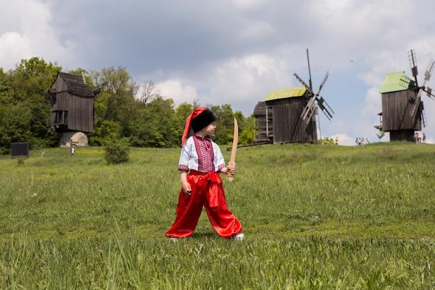 Śliczny kozak w haftowanej ukraińskiej koszuli. dziecko w strojach ludowych podczas ukraine.national museum pirogovo w plenerze pod kijowem