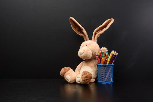 Śliczny króliczek siedzieć na tle czarnej tablicy kredowej, powrót do szkoły, miejsce