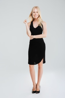 Śliczny ładny uśmiechnięta młoda kobieta w czarnej sukience i butach stojących na białym tle