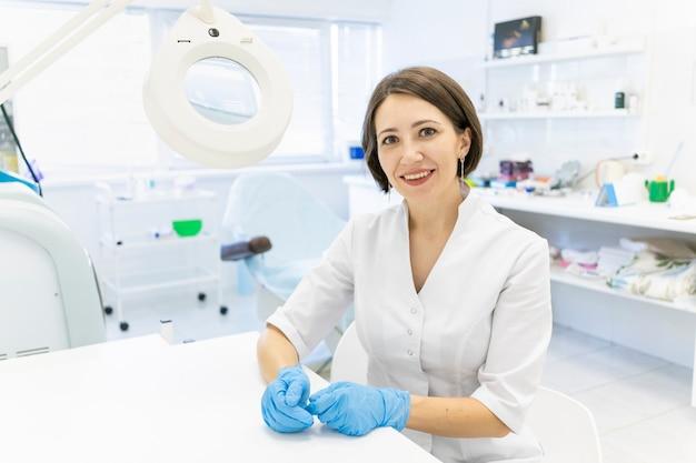 Śliczny lekarz w białym fartuchu kosmetolog siedzi w gabinecie i uśmiecha się w powiększeniu