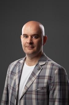 Śliczny łysy mężczyzna w kurtce i koszulce pokazuje na szarej ścianie