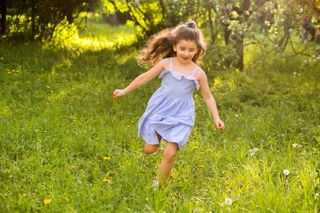 Śliczny mała dziewczynka bieg w ogródzie
