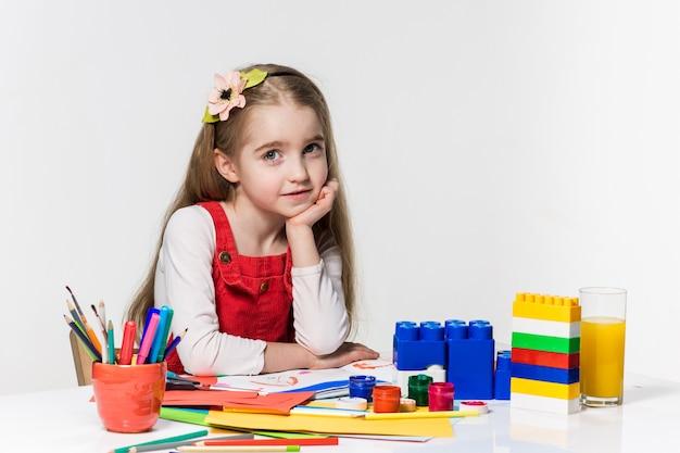 Śliczny mała dziewczynka rysunek z farbą i paintbrush w domu