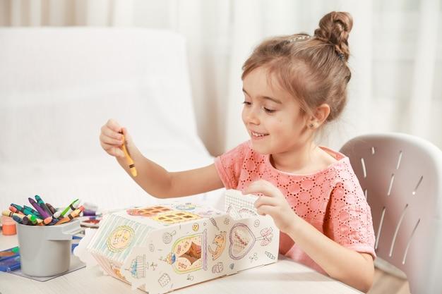 Śliczny mała dziewczynka rysunek z ołówkami w domu