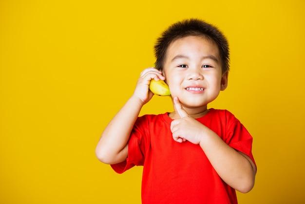 Śliczny małe dziecko chłopiec uśmiech bawić się trzyma bananową owoc udaje być jak telefon