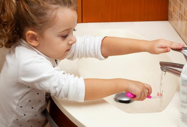 Śliczny małej dziewczynki cleaning ząb z muśnięciem.