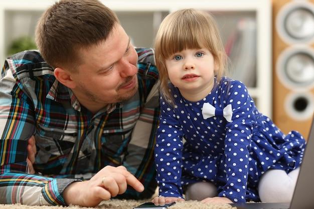 Śliczny małej dziewczynki obsiadanie na podłogowym dywanie z tata